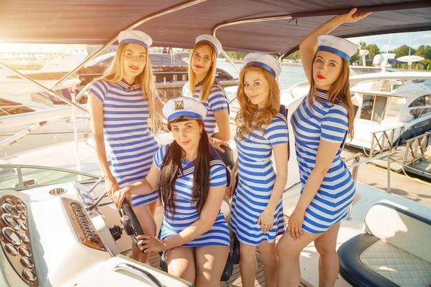 Amici di ragazze su uno yacht in abiti a righe e cappellini
