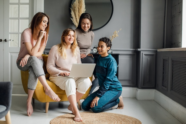 Concetto online di acquisto di amicizia delle ragazze. quattro bellissime amiche siedono a casa e ordinano su internet.