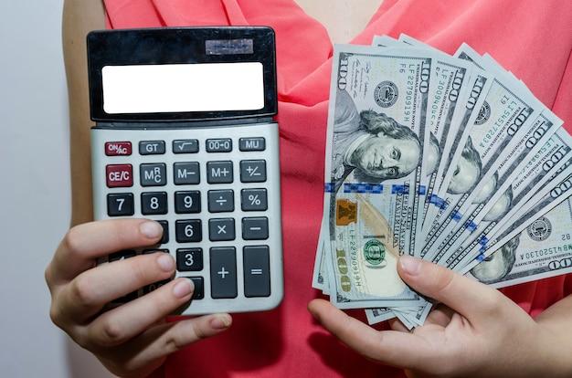 Le mani delle ragazze tengono una calcolatrice con una lavagna bianca e dollari