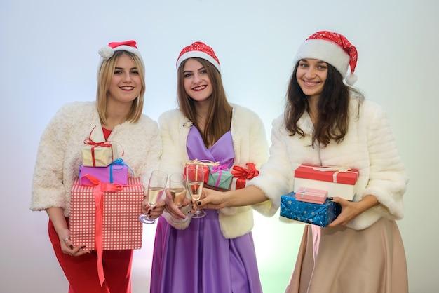 Ragazze in possesso di scatole regalo e bicchieri di champagne. concetto di celebrazione del nuovo anno