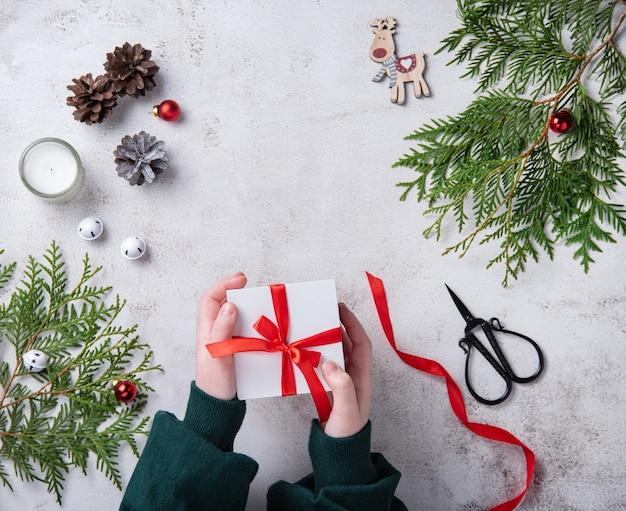 Ragazze che tengono regalo di natale bianco con nastro rosso sul tavolo grigio chiaro. sfondo di natale con albero di tuia, coni di candele e giocattoli di natale. vista piatta e dall'alto