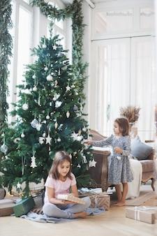 Ragazze a casa durante il natale con albero e regali