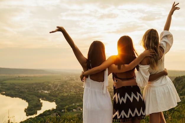 Ragazze che abbracciano in cima alla collina con il fiume