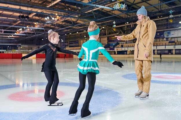 Le ragazze nella lezione di pattinaggio sul ghiaccio
