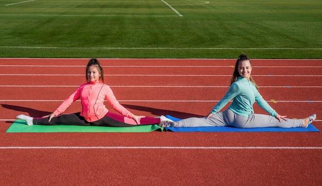 Le ragazze che allenano lo sport all'esterno dell'arena dello stadio siedono divise, allungando.