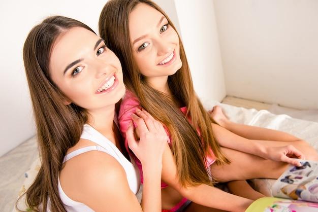 Ragazze in pigiama seduti sul letto a leggere riviste