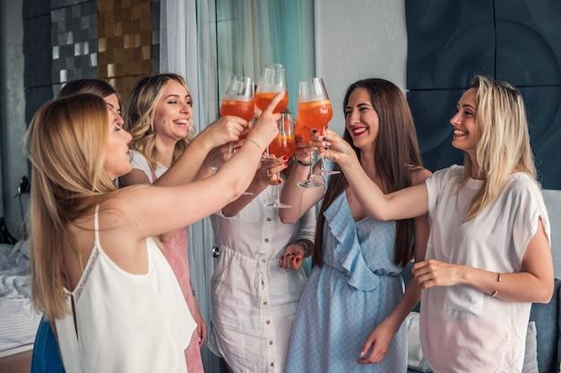 Festa delle ragazze. belle amiche che si divertono alla festa di addio al nubilato. stanno festeggiando e bevendo champagne all'addio al nubilato. saluti