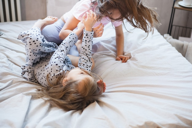 Ragazze che giocano a letto a casa durante il natale