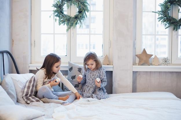 Ragazze che giocano a casa sul letto durante il natale