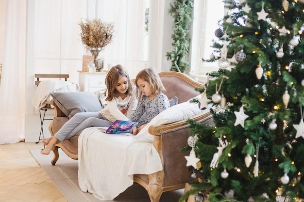 Ragazze che leggono un libro accanto all'albero di natale