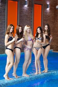 Ragazze che si rilassano in piscina con champagne.