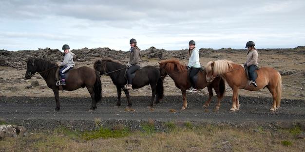 Ragazze in sella a caschi di fila su cavalli islandesi