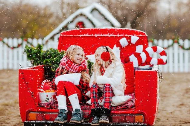Ragazze sedute nell'auto aperta rossa con albero e decorazioni nevicata