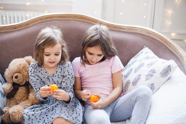 Ragazze sedute sul divano di casa a natale