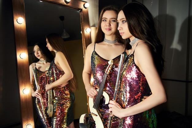 Ragazze in abiti scintillanti con violini
