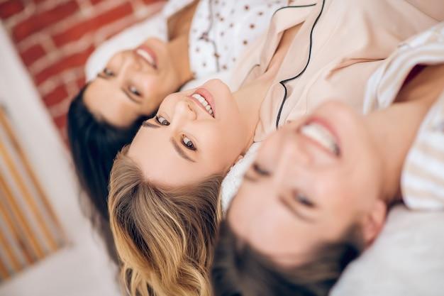 Ragazze. tre belle ragazze che scherzano sul letto e sorridono