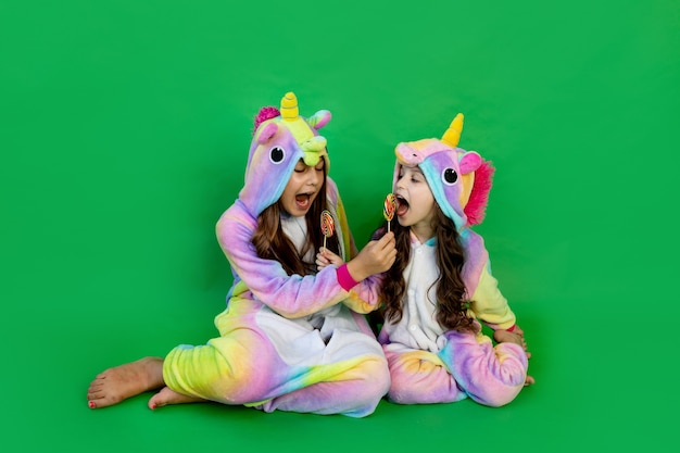 Ragazze in costume da unicorno che mangiano lecca-lecca