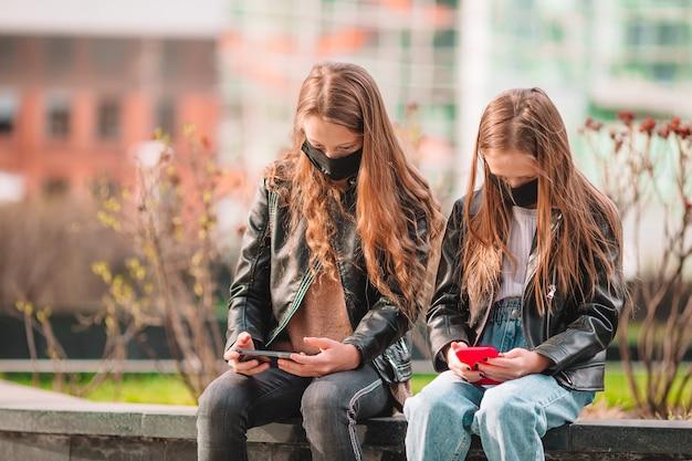 Ragazze che indossano una maschera all'aperto per prevenire virus e giocare con lo smartphone.