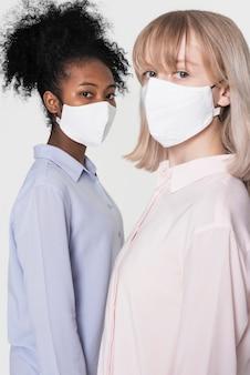 Le ragazze che indossano una maschera bianca il nuovo normale servizio di moda con spazio di design