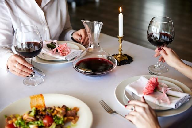 Ragazze con bicchieri di vino rosso sono sedute a un tavolo servito in un ristorante
