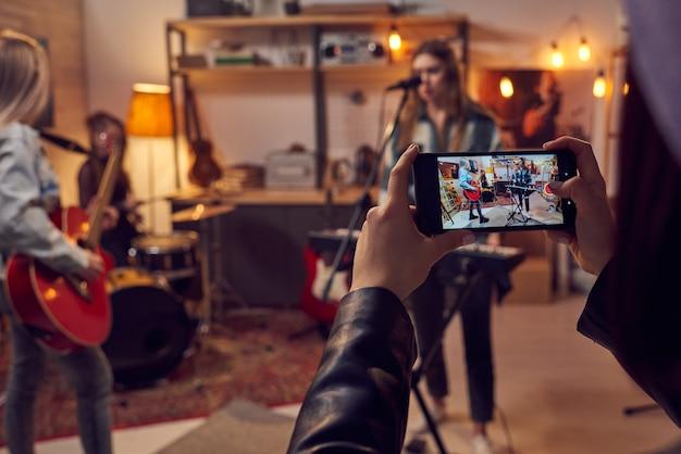 Ragazze con smartphone che riprendono video della sua band che suona strumenti musicali in studio