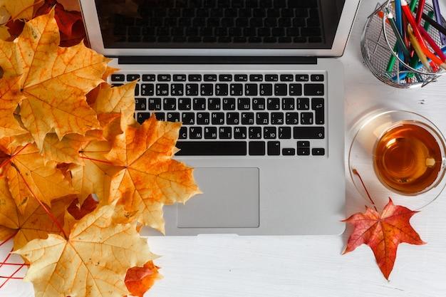 Desktop dell'ufficio femminile con lo schermo bianco in bianco del computer portatile, i fiori, il caffè, lo smartphone e vari strumenti dell'ufficio. modello