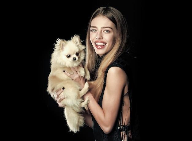 Gitl con la donna del cane gioca con l'animale domestico dell'animale domestico alla donna isolata sulla ragazza nera con la faccia felice e capelli lunghi tiene la bellezza del cucciolo e la donna di modo con lo spazio della copia dello spitz di pomerania