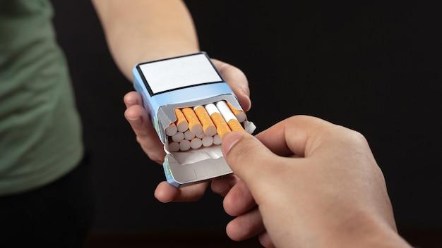 Dare una sigaretta da un pacchetto, primo piano della dipendenza da nicotina.