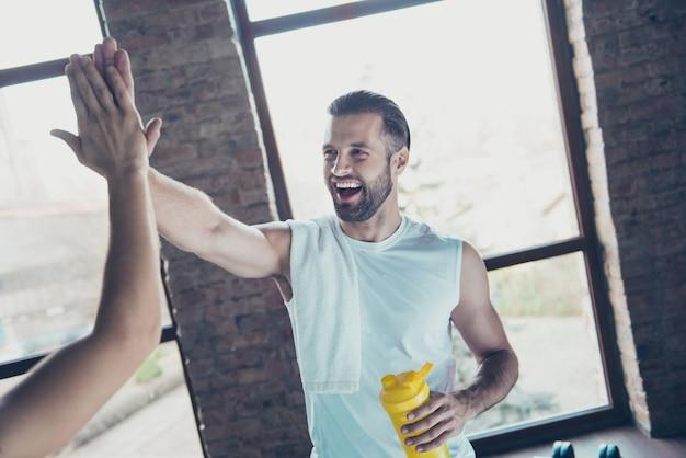 Dammi il cinque! foto di mattina di ragazzo allenatore sportivo bello che si esercita in attesa asciugamano bottiglia d'acqua amichevole sorridente alle finestre di casa formazione canotta di abbigliamento sportivo cliente al chiuso