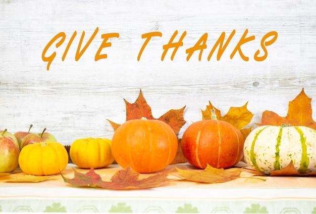 Dare grazie testo scritto a mano. giorno del ringraziamento con frutta e verdura sul tavolo. raccolto autunnale