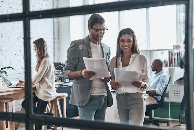Dare consulenza aziendale. gruppo di giovani moderni che lavorano e comunicano insieme stando in piedi dietro la parete di vetro nella sala riunioni