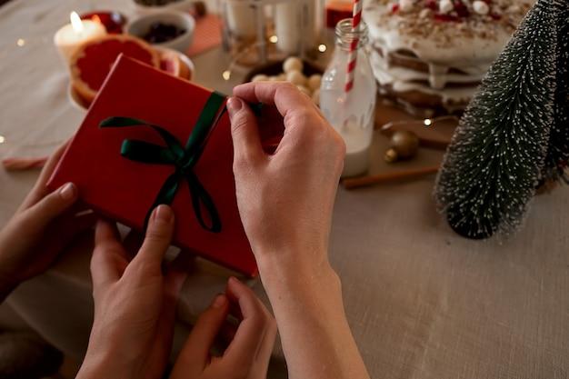 Fare regali di natale. mani di donna e bambino che tengono una piccola scatola regalo rossa con fiocco verde. avvicinamento.