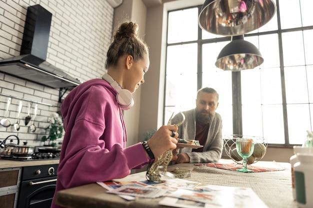Dare cibo. padre barbuto premuroso che dà a sua figlia il piatto con il cibo seduto in cucina