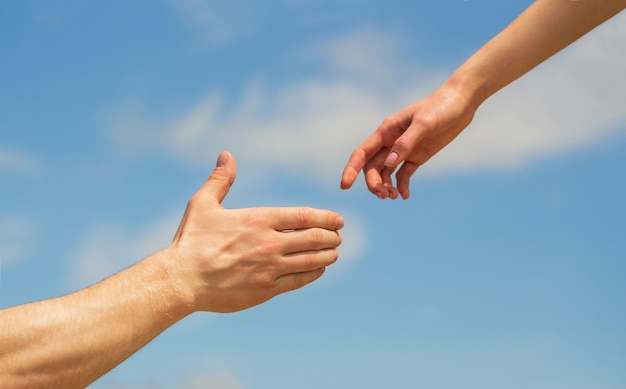 Dare una mano. mani dell'uomo e della donna sul cielo blu. dare una mano.