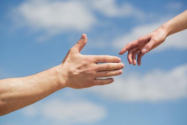 Dare una mano. mani dell'uomo e della donna sul cielo blu