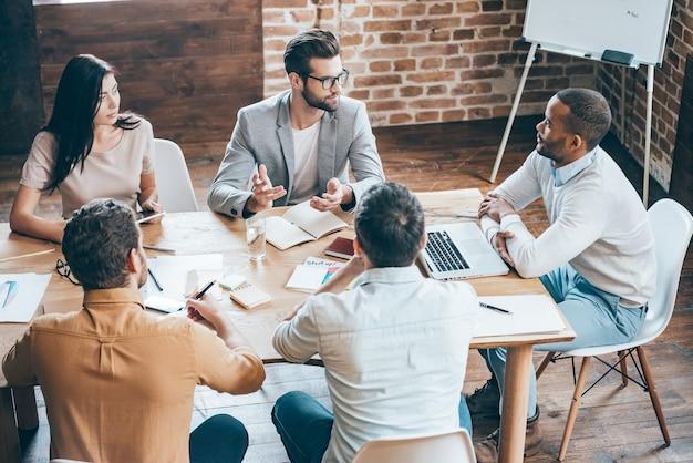 Dare alcuni consigli ai colleghi. vista dall'alto di giovani uomini d'affari che discutono di qualcosa mentre sono seduti insieme alla scrivania dell'ufficio