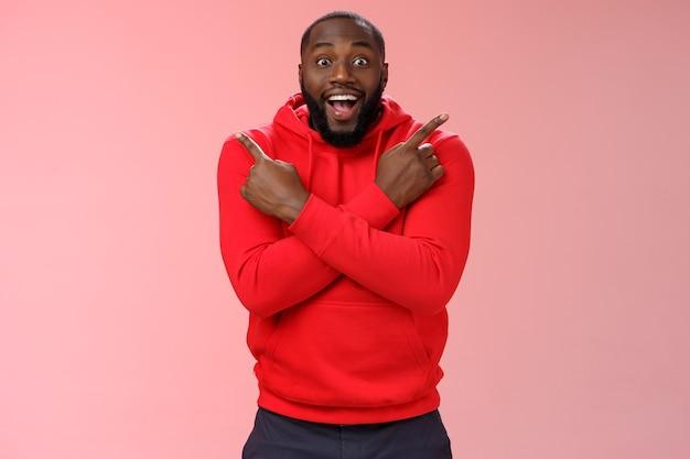Felice stupito di bell'aspetto felice cliente maschio nero barbuto spalanca gli occhi sorpreso con gioia indicando entrambi i lati sinistra destra braccia incrociate petto impressionato varietà prodotti freschi, in piedi sfondo rosa