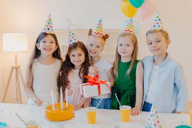 La ragazza di compleanno felice sta con presenet, gli amici felici vengono a congratularsi con lei, indossano cappelli a cono di festa, stanno vicino al tavolo festivo con la torta