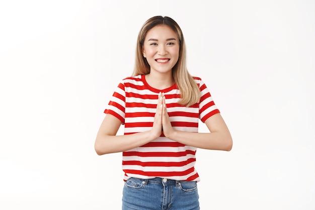 Felice allegra positiva ragazza bionda asiatica premere i palmi insieme pregare gesto di supplica sorridente compiaciuto grato grato regalo piacevole, in piedi muro bianco