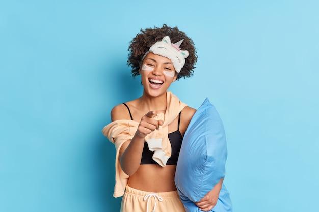 Felice donna etnica dai capelli ricci sorride ampiamente punta il dito contro di te ride per qualcosa di divertente vestito in pigiama porta morbido cuscino sotto il braccio si prepara per il sonno e il riposo