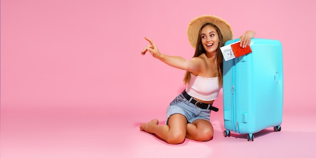 Felice ragazza con la valigia, i biglietti, i soldi e il passaporto viaggeranno puntando il dito