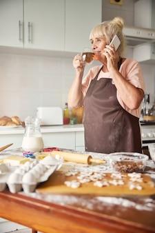 Felice nonna che prende il telefono mentre beve il tè