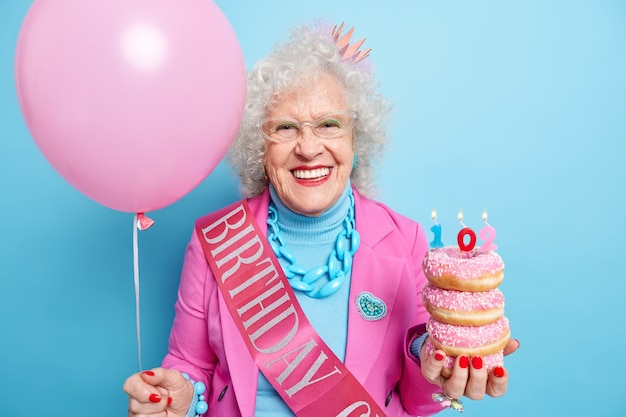 Felice donna ottimista festeggia il 102 ° compleanno tiene una pila di ciambelle e un palloncino di elio gonfiato vestita con abiti festivi sembra bella ben curata indossa un trucco luminoso