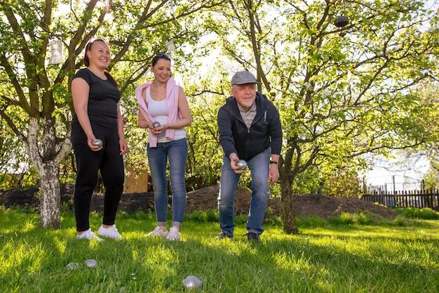 Felice positivo famiglia sorridente giocando francese gioco tradizionale bocce in un giardino esterno durante la bella giornata estiva godendo il tempo libero