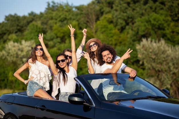 Felice alla moda giovani ragazze dai capelli scuri e ragazzi in occhiali da sole sorridono in una cabriolet nera sulla strada alzando le mani in una giornata di sole. .