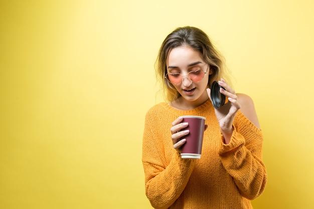 Donna glamour con gli occhiali in un maglione arancione con una bevanda di caffè su sfondo giallo