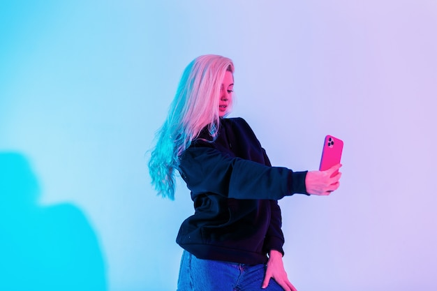 Bella donna alla moda affascinante in felpa con cappuccio casual nera con jeans fa selfie su uno smartphone in studio su uno sfondo blu-rosa multicolore