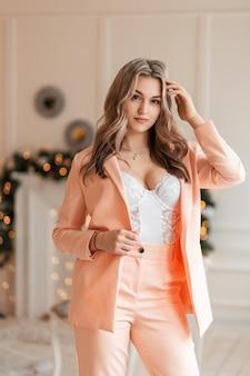 Affascinante bella giovane donna calda con bei seni sexy in un vestito alla moda e blazer con body in pizzo su uno sfondo di luci gialle al chiuso