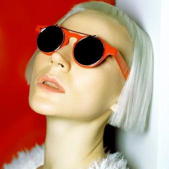 Acconciatura alla moda bionda affascinante e occhiali da sole alla moda.