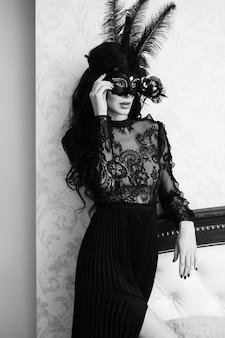 Affascinante signora bruna con una bella acconciatura e labbra rosse, in un abito da sera, una maschera nera veneziana con accessori alla moda